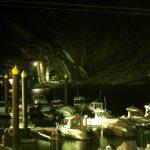 Vista nocturna de embarcaciones amarradas a puerto